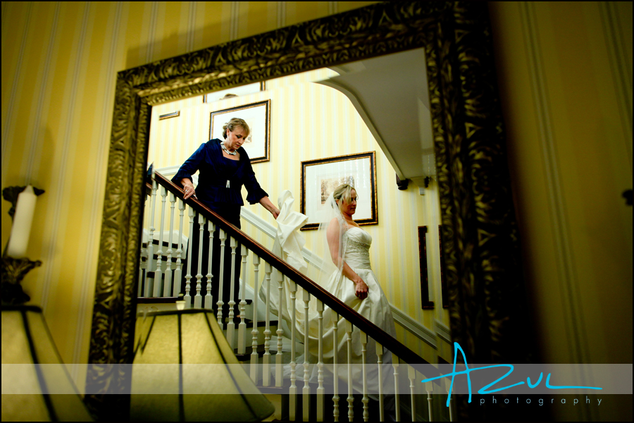 Photograph of bride descending down stairs as she heads to her wedding in Wilson, North Carolina. The photographer framed the bride in a mirror.