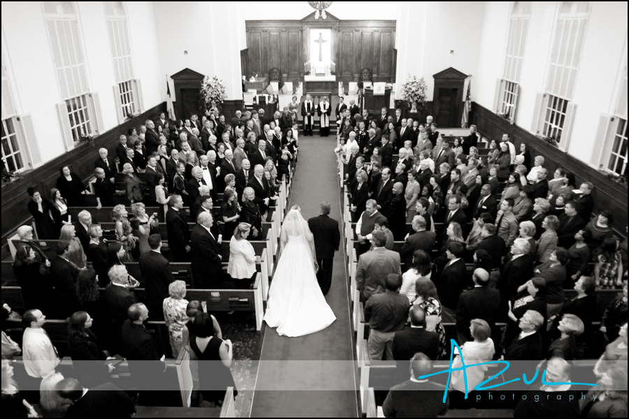 The photographer documents Jennah walking down the aisle as everyone stands for the bride while in the First Presbyterian Church in Wilson.