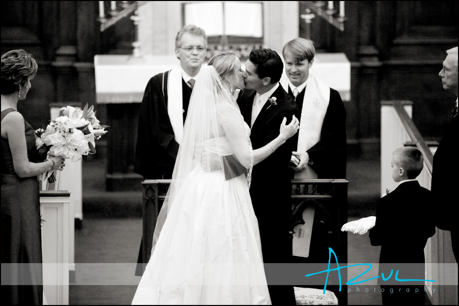 The bride kisses the groom while at their Wilson wedding at First Presbyterian Church.