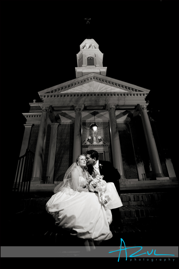 The bride and groom sit on the front steps of the church and share a kiss before heading to the reception.