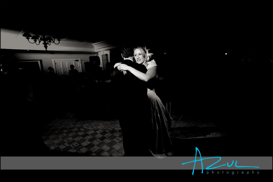 The bride holds on to her husband as they embrace on another on the dance floor.